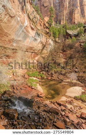 The water falling from the edges of the mountain cliffs at Zion National Park on the path through the Emerald Pools. - stock photo