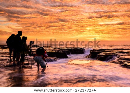The wave flows over weathered rocks and boulders with group of photographer at North Narrabeen rockshelf in sunrise. Sydney Australia - stock photo