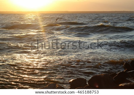 The waves beat against the rocks on the shore of a lake in a storm