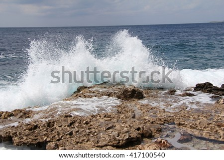The waves breaking on a stony beach, forming a spray. Wave and splashes on beach. Waves crashing onto rocks.  - stock photo