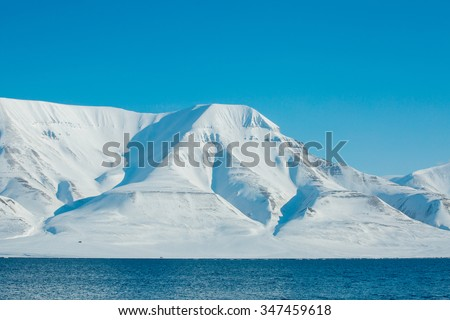 The waves of the Arctic Ocean and the snow-capped mountains of the Spitsbergen archipelago.