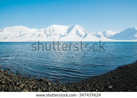 The waves of the Arctic Ocean and the snow-capped mountains of the Spitsbergen archipelago. - stock photo