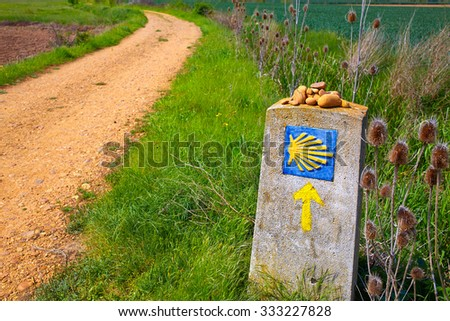 The Way of Saint James shell sign and yellow arrow in Castilla Leon of Spain - stock photo