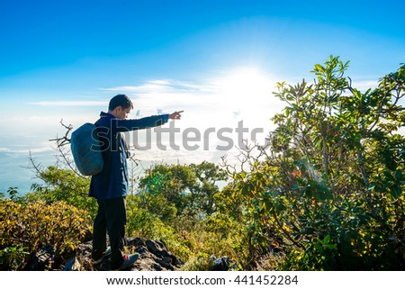 The way to freedom, Young man with backpack taking a photo on the top of mountains, Sub alpine green forest - stock photo