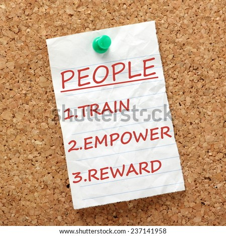 The way to success with your people or staff is to Train, Empower and Reward as per this reminder attached to a cork notice board  - stock photo
