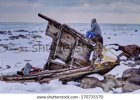 The Weary traveler. Teenaged male sitting on rock stranded in a desolate landscape, with a beached shipwreck in the foreground.  Sanilac County Park. Lexington, Michigan. - stock photo