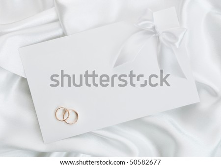 The wedding invitation with wedding rings on a white background