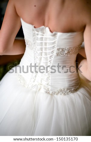 The wedding morning with close-up of gorgeous wedding dress and back of bride - stock photo