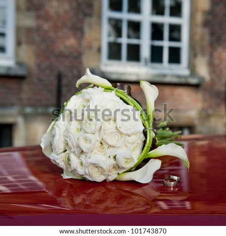 The wedding rings and a bouquet of the bride laying on the hood of a red car. - stock photo