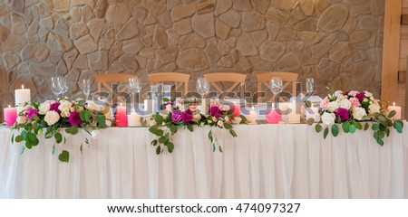 The wedding table of newlyweds decorated with fresh flowers and the burning candles