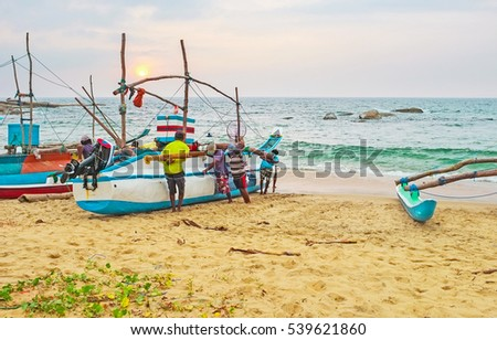 The weekdays of Sri Lankan fishermen, going to the sea before the sunrise and back to the harbor on sunset, steering their heavy boat to the sand, Hikkaduwa.