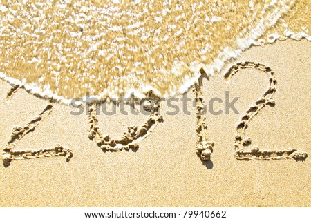 The welcome of the new year 2012; message in the sand at the beach near the ocean - stock photo