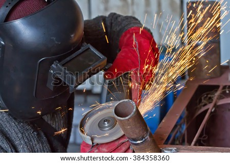 The welder handles the root seam with a cutting machine. Preparing for the facing seam to the control sample. - stock photo