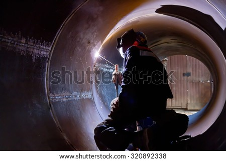 The welder weld root weld from inside of the housing of  chemical apparatus - stock photo