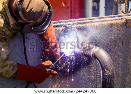 The welder welds the design of the pipes. Sunny day.