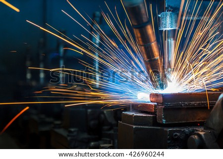 The welding robots represent the movement in the automotive parts industry - stock photo