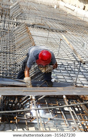 The welding worker in the construction site making reinforcement metal framework for concrete pouring - stock photo