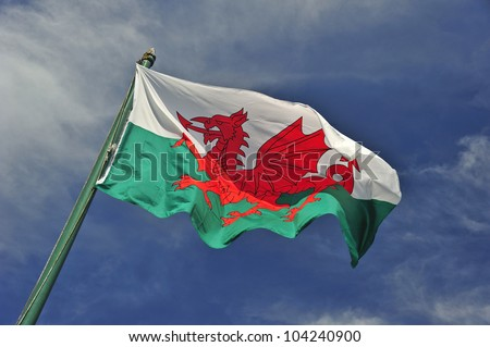 The Welsh flag against a blue sky. Motion blur at the tip of the flag. Space for text in the sky. - stock photo