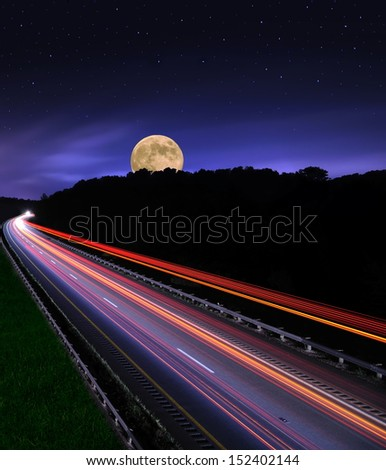 The westbound lane of Ohio Interstate 70 under a starry, moonlit sky.The image was shot with a slow shutter speed making the traffic appear as streaks of light.  - stock photo