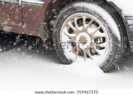 The wheels of the car in the snow - stock photo