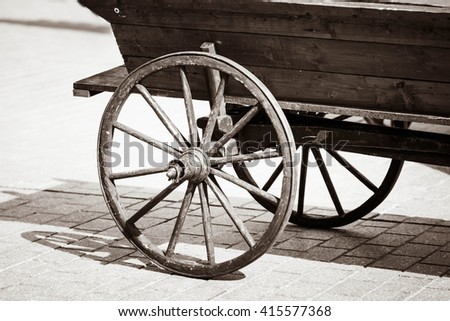 the wheels of the coach car truck in a rustic retro vintage style old background. Settler - stock photo