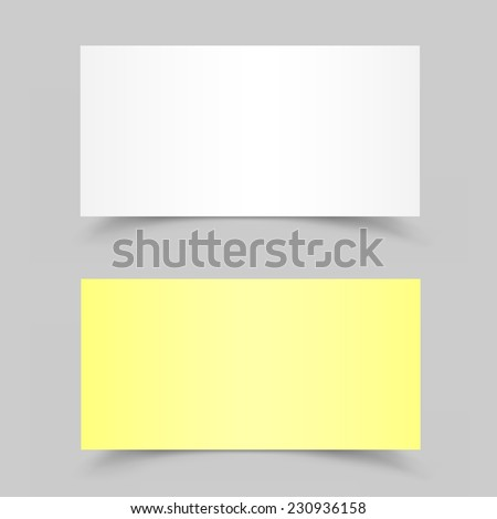 The white and yellow pieces of paper on the gray background - stock photo