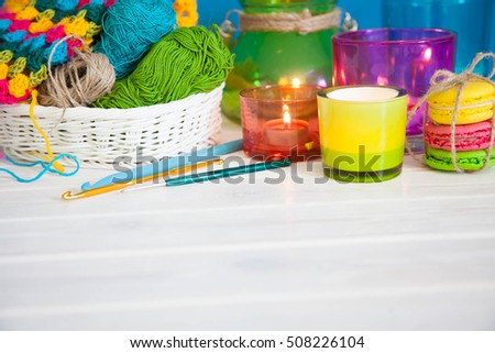 The white basket crochet fabric and colored yarn. Candles in candlesticks color. Background of white wood. Tea and cakes. Crochet hooks.