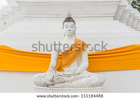 The white buddha with yellow robe - stock photo