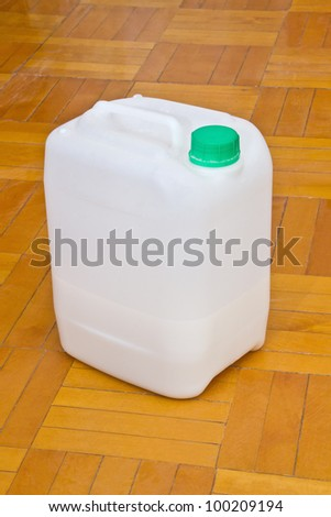 The white canister with a green cap standing on the parquet floor - stock photo