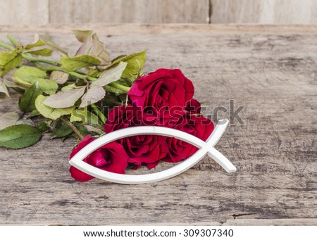 the white christian fish  with  red roses  on wooden background - stock photo