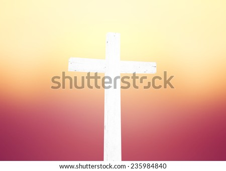 The white cross over blurred sunset background. - stock photo
