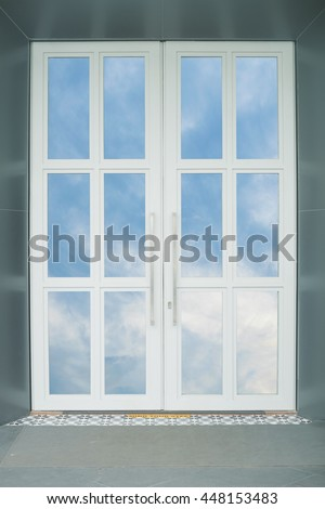 The white door reflect the sky on glasses.