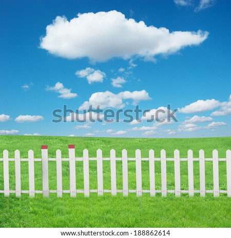 The white fence and green grass under blue sky and white clouds.