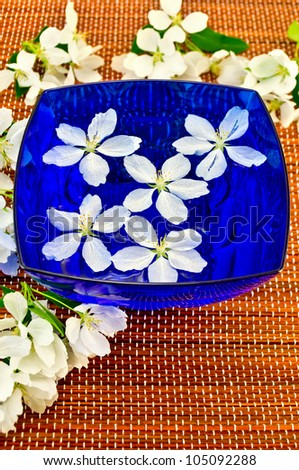 The white flowers of apple trees in the blue cup with water and brown bamboo mat