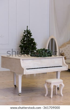 the white grand piano stands in in the light room - stock photo