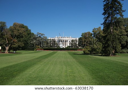 The White House in Washington DC with green lawn and beautiful blue sky - stock photo