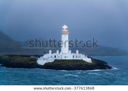 The white lighted lighthouse of Lismore at dusk in a storm, near Mull and Oban, in the Inner Hebrides of Scotland. The lone beacon gives guidance, warning, safety to ships at sea near the dim coast. - stock photo