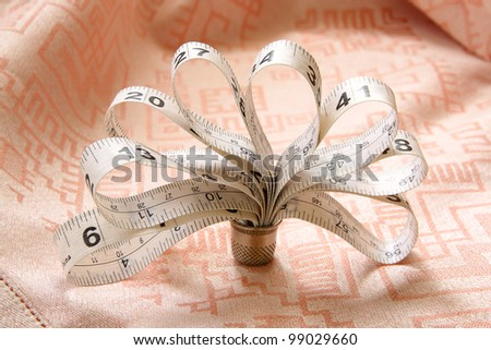 The white measuring tape for sewing in the form of a flower in a thimble on pink fabric - stock photo