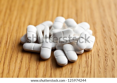 the white pills on wooden table - stock photo