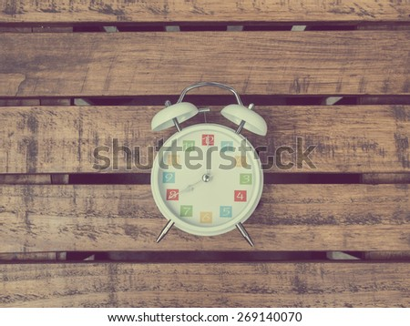 The  white retro alarm clock with colorful number is showing 8 o'clock on wooden background in vintage style. - stock photo