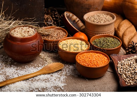 The white rice, black eyed peas, lens, beans and buckwheat in ceramic bowls on the table - stock photo