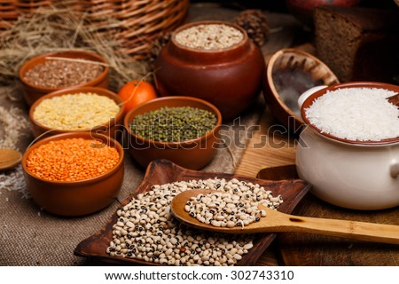 The white rice, black eyed peas, lens, beans and buckwheat in ceramic bowls on the table