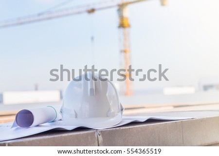 White safety helmet blueprint on table stock photo 554365519 the white safety helmet and the blueprint on the table at construction site with crane background malvernweather Gallery