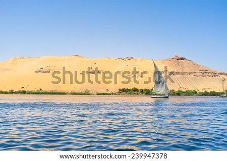The white sail of felucca with the rocky Nile bank on the background, Aswan, Egypt.
