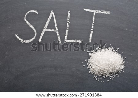 the white salt on chalkboard - stock photo
