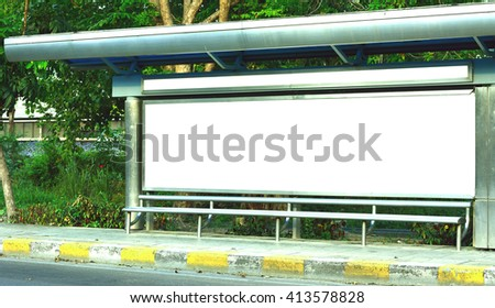 The white sign board on the bus stop wiih green tree background near old road