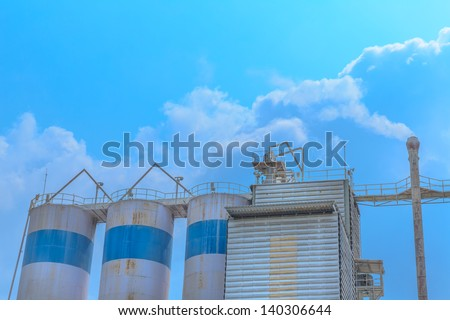 the white smoking chimney of a lime industry against a white cloud and blue sky. - stock photo