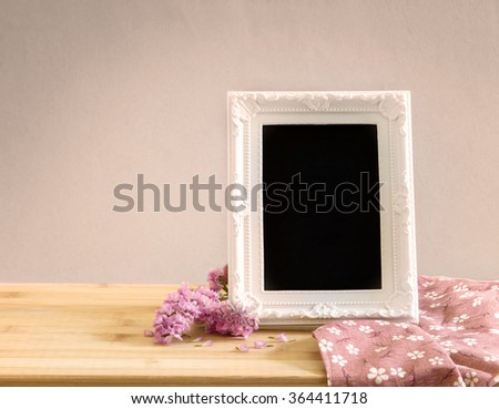 The White vintage photo frame with sweet statice flower  on wooden table , romance concept - stock photo