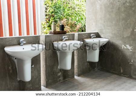 The white washbasin in public toilet - stock photo