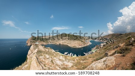 The wide angle panoramic view from ruins of ancient Genoese fortress on Kastron cliff top above the entrance to the Balaklava Inlet towards Balaklava town, Sevastopol, Crimea. - stock photo